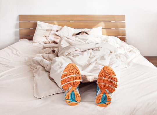 person in bed with jogging shoes and knee sleeves