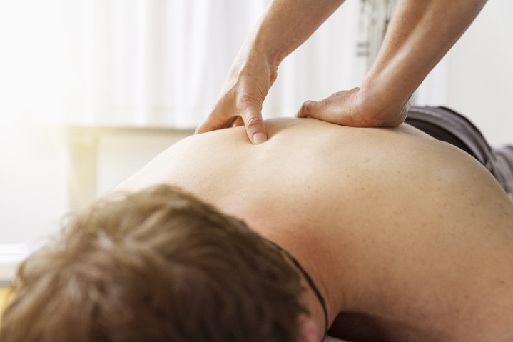 Woman probing back for trigger points to massage